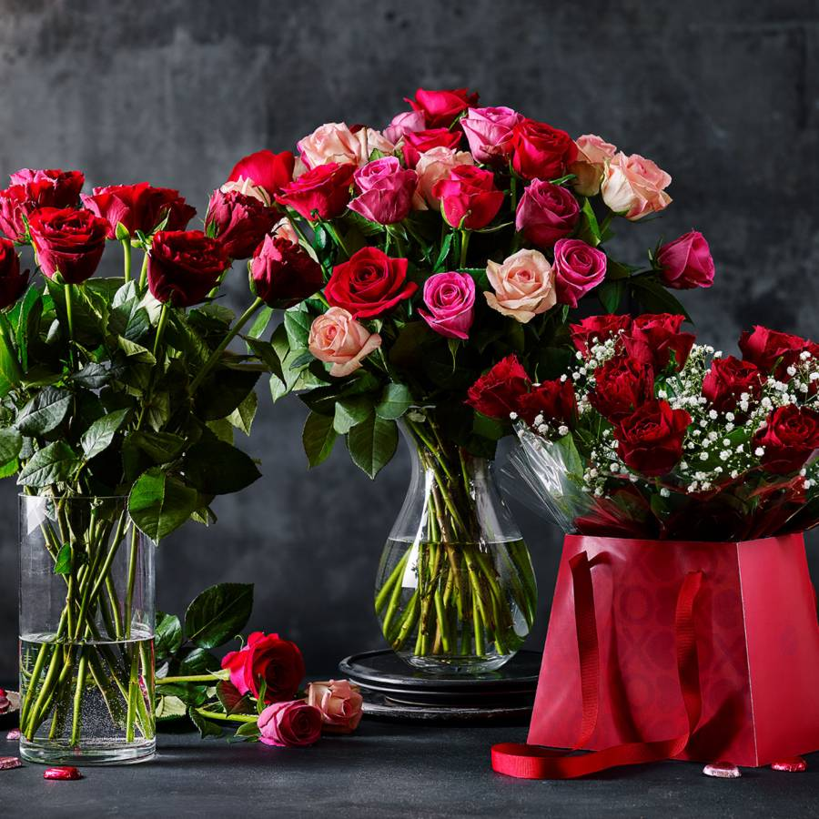 three bouquets of roses, two in a vase and one in a gift box.