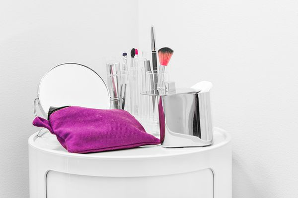 Kuvassa soma säilytyskaluste, jonka päällä peili ja meikkisiveltimiä.