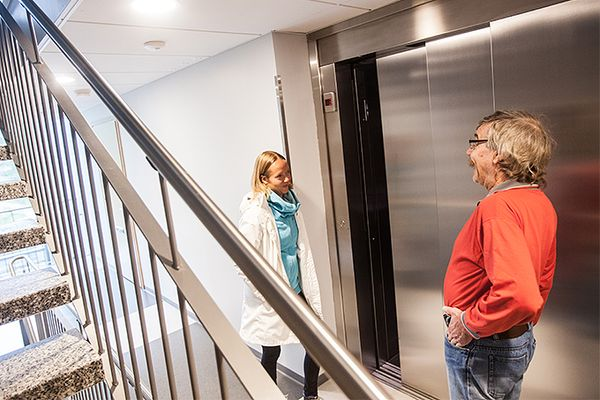Hanni Kärkkäinen ja Matti Ahonen porraskäytävässä hissin edessä.