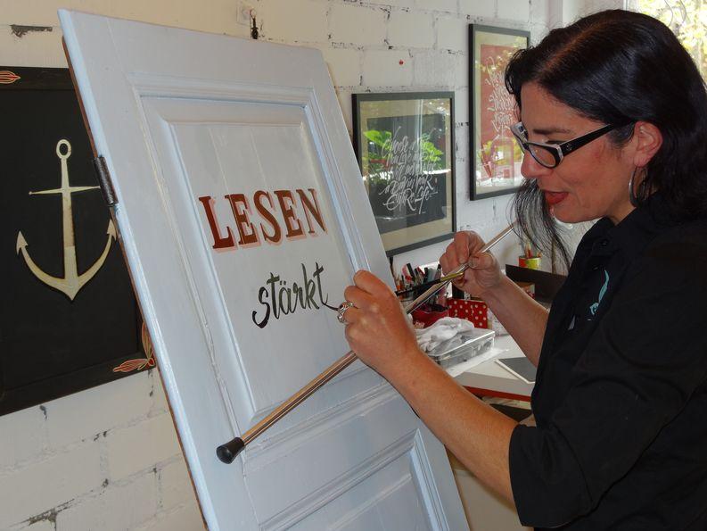 Laila Luisi vollendet eine Kalligraphieschrift mit Pinsel und Malstock, der ein sicheres Abstützen der Hand erlaubt. Das Wort «Lesen» ist formal gezeichnet und ausgemalt.