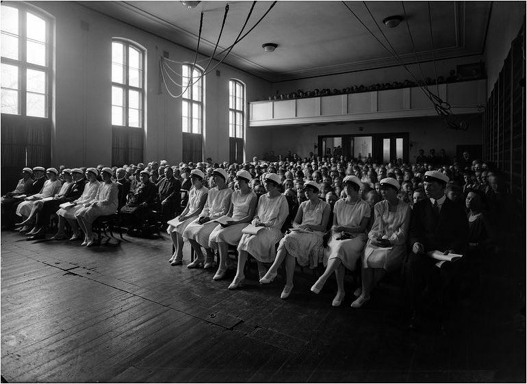 1927 Lisa Hagmanin yksityisluokat -nimisen koulun ensimmäiset ylioppilaat ja juhlayleisöä koulun juhla- ja voimistelusalissa. Kuva: Helsingin kaupunginmuseo, valokuvaaja Eric Sundström.