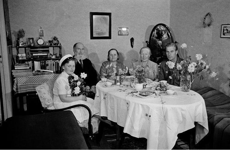 Ylioppilaaksi päässyt nuori nainen ja perhe kotona katetun kahvipöydän ympärillä 1946. Kuva: Helsingin kaupunginmuseo, valokuvaaja Väinö Kannisto.