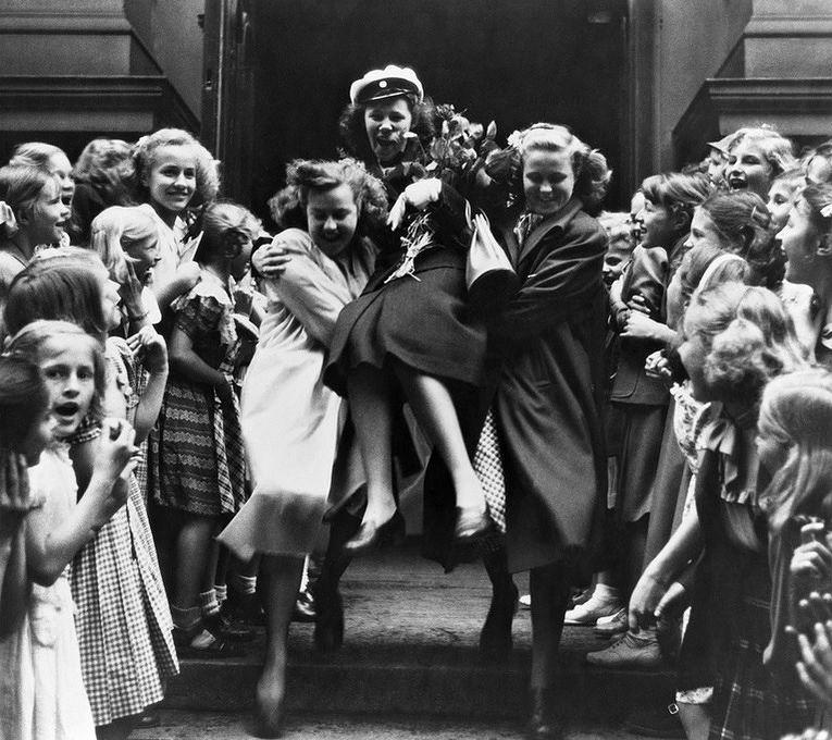 1949 tuoretta ylioppilasta kannetaan kultatuolissa ulos Svenska flicklyceet'istä. Kuva: Helsingin kaupunginmuseo, valokuvaaja Hugo Sundström.