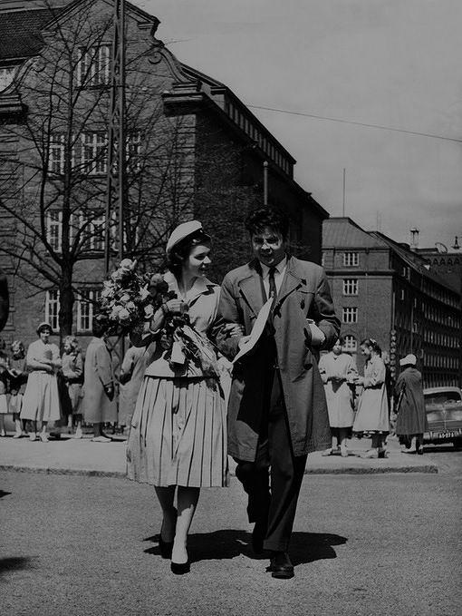 Tyttönormaalilyseon ylioppilas kavaljeerinsa kanssa 1954. Lakkiaispäivä Runeberginkadulla Töölössä. Elanto-lehden kuva.Kuva: Helsingin kaupunginmuseo, valokuvaaja Arvi Jokinen.