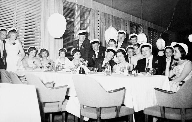 Helsingin Uuden yhteiskoulun uudet ylioppilaat lakkiaispäivällisellä ravintola White Ladyssa 1957. Juhlijoista vain yksi tupakoi. Kuva: Helsingin kaupunginmuseo, valokuvaaja tuntematon.