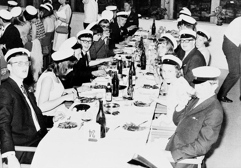 Arkadian yhteislyseon ylioppilaat lakkiaispäivällisellä Dipolissa 31.5.1967. Etummaiset pojat teeskentelevät humalatilaa, ateria on vasta alkamassa. Kuva: Helsingin kaupunginmuseo, valokuvaaja tuntematon.