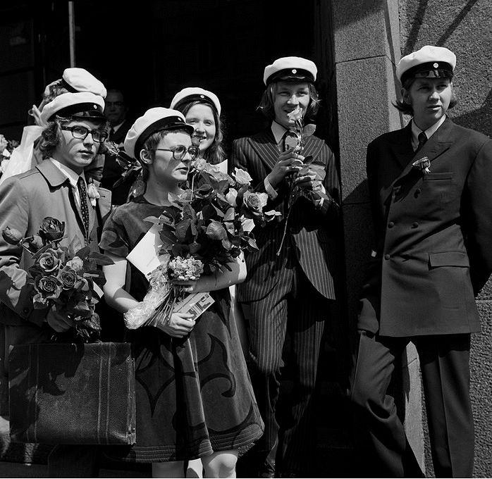 Suomalaisen yhteiskoulun uusia ylioppilaita ruusukimput sylissään koulunsa edustalla 1971. Kuva: Helsingin kaupunginmuseo, valokuvaaja Kari Hakli.
