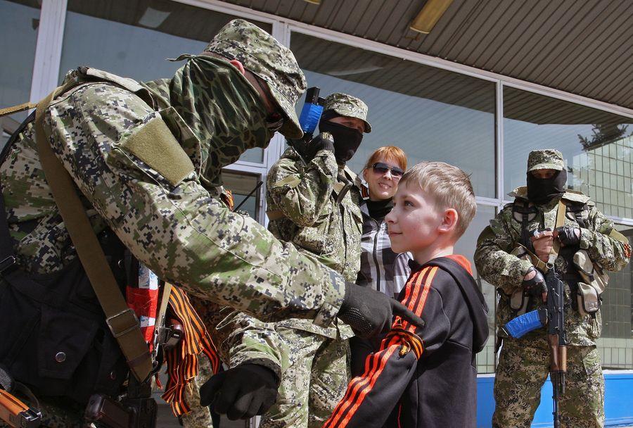 Venäläismielinen separatisti sitoo Yrjön nauhaa huhtikuussa 2014 Itä-Ukrainassa tms. Kuva: Igor Kovalenko.
