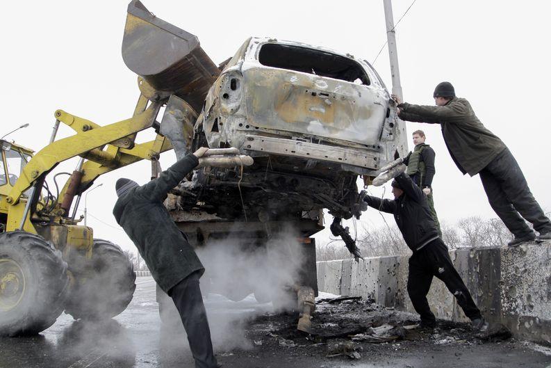 Taisteluissa tuhoutunutta autoa siirretään Donetskissa 10. helmikuuta. Kuva: Alexander Ermochenko/EPA