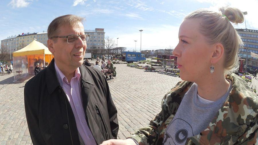 Lauri Lyly kertoo toimittaja Eve Väyryselle työväen vappuhuolista Hakaniemen torilla.