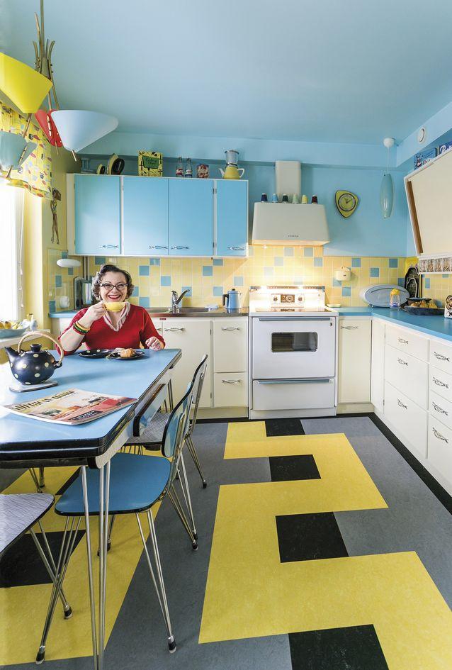 1950-lukua from tip to toe. Sylvie Jussila istuu teellä keittiössään, jonka kaapistot ovat Kvänumin uustuotantoa. Lattian kuvion malli on otettu ajan sisustuslehdestä. Kodin monet kalusteet ja pienesineet on kerätty Suomesta ja ulkomailta 25 vuoden aikana. Kuva Antti Kuparinen.