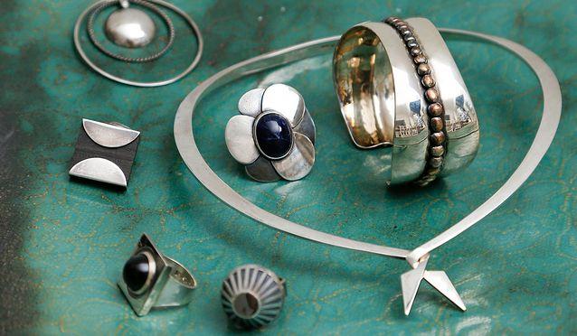 Börje Rajalinin yksinkertaiset kivillä ja ornamenteilla koristellut hopeakorut toivat modernit hopeakorut suosioon 1950-luvulla. Rajalinin käsin taotun juhlakäädyn sisällä on Eila Minkkisen Villiruusu ja vieressä Bertel Gardbergin kalvosinnappi.