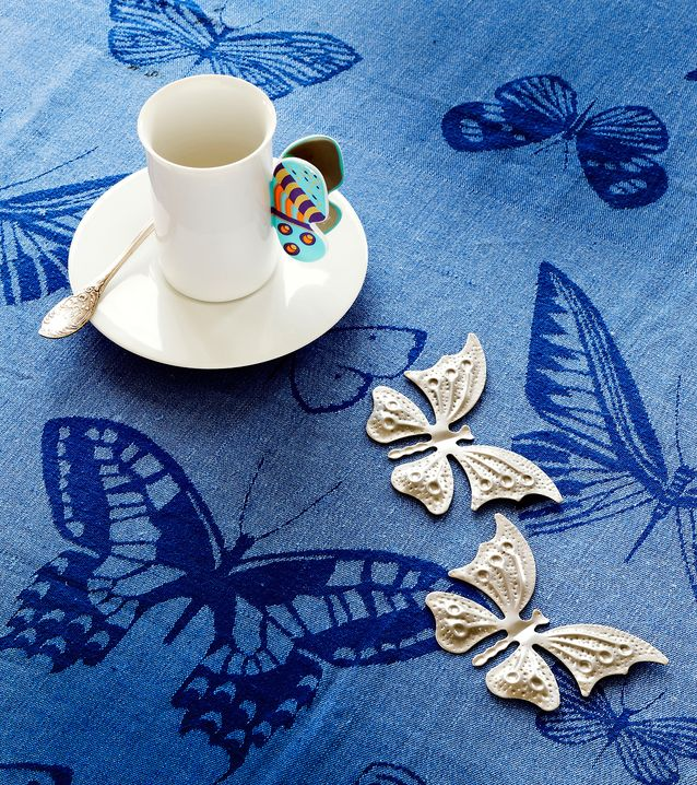 Nanny Stillin saksalaiselle Rosenthalille suunnitteleman keräilykupin korva on veistoksellinen perhonen, 120 e, Brummer & Brummer. Pöytäliina on Dora Jungin 1960–70-luvun mallistoa, 90 e, Vanhaa ja Kaunista. Metalliset suklaamuotit 5 e / kpl, M. Suominen.