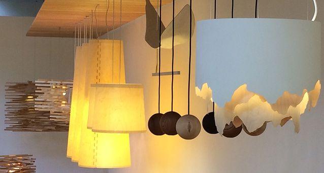 Puusta syntyy pehmeää valoa antavia valaisimia. Etummaisen Aava-kattovalaisimen on suunnitellut Laura Väre ja se on toteutettu Aalto-yliopiston puustudion valaisinkurssilla.