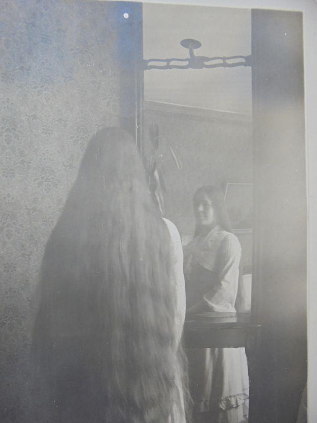 Intiimi hetki ikuistettuna yksityiseen albumiin. Rakastuneen aviomiehen kuvaama vaimo avaa illalla hiuksensa nutturalta. Gerda Kjäldström (os. Jernström) vuonna 1914.