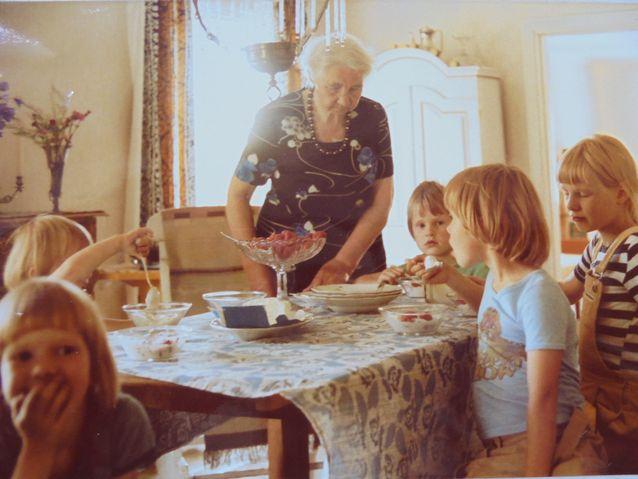 Kuva salista. Olen kuvassa etualalla käsi suun edessä Helena- täti oli aina pukeutunut leninkiin ja jalassaan hänellä oli korkeakorkoiset kengät. Taustalla vaalea astiakaappi ja pöydän yllä hieno lasivalaisin. 