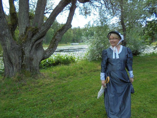 Ihastuttava oppaamme Katarina Zaharov eli Tarja Kvarnström kylpyläpuiston lammen äärellä. Lampi on ollut aikoinaan suurempi ja siihen on istutettu kaloja.
