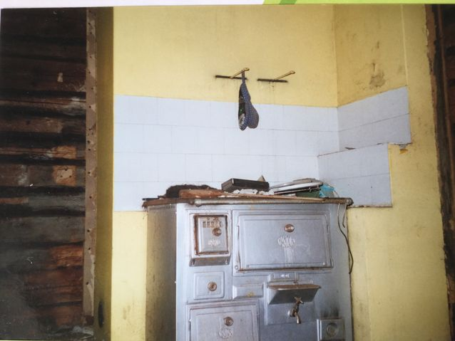 Purettua seinää ja viimeinen kuva keittiön vanhasta puuhellasta. Yksinäinen kirjailtu patalappu roikkuu sen yläpuolella. Se pelastettiin.