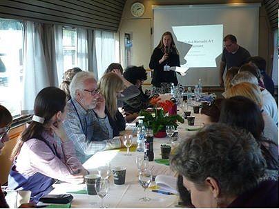 Kuva junakongressimatkalta keväällä 2015. Puhujavuorossa on tutkija Liettuasta. Mukana tutkijoita USA:sta, Ruotsista, Venäjältä, Irlannista ja Suomesta. Ikkunassa vilisee Etelä-Pohjanmaan maisema. Kuva: Kate Berenson.