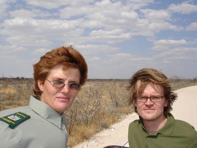 Janne Hopsu poseeraa riistanvartijan kanssa auton lavalla Etoshan luonnonpuistossa Namibiassa.