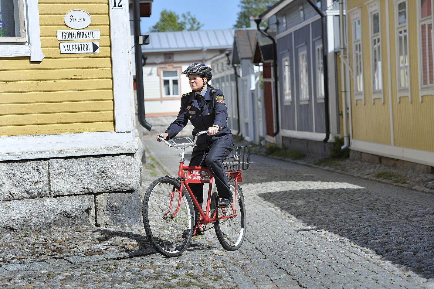 Palomestari Mirva Torvinen kurvailee kesäisin Vanhan Rauman kaduilla punaisella palokunnan polkupyörällä.