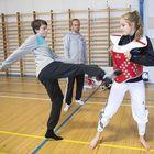 Kiukaisten yhteiskoulun 8.-luokkalainen Tero Saarivuori pääsi kokeilemaan taekwondopotkua Noora Rannikon rintaan. Taustalla kannustaa isä Jari Saarivuori sekä ohjaaja Erik Pohjonen.