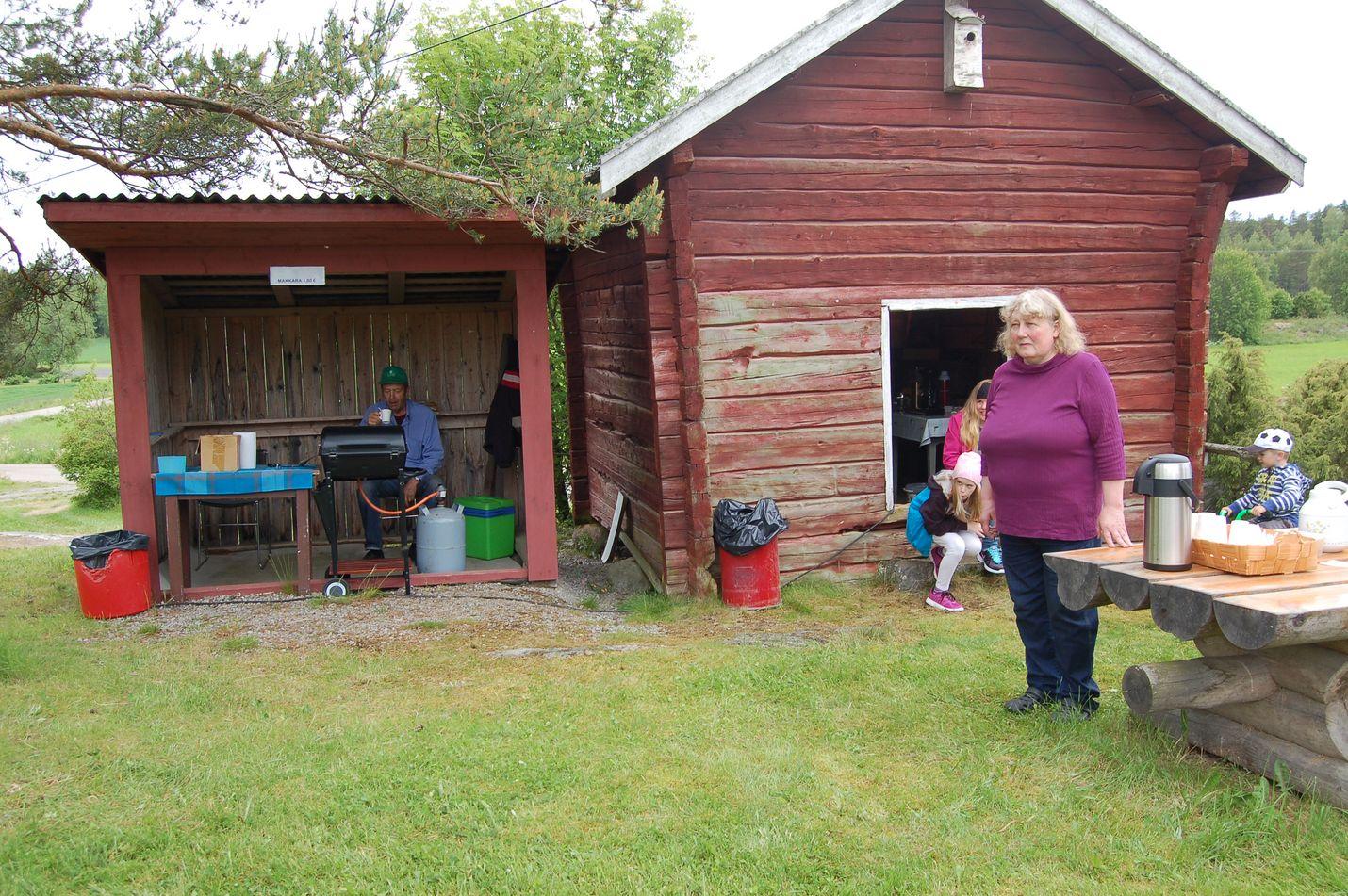 Juhannusjuhlilla oli tarjolla myös makkaraa ja kahvia. Tärkeintä monille tapahtumassa on muiden kyläläisten tapaaminen. Kuva: Elina Lammela