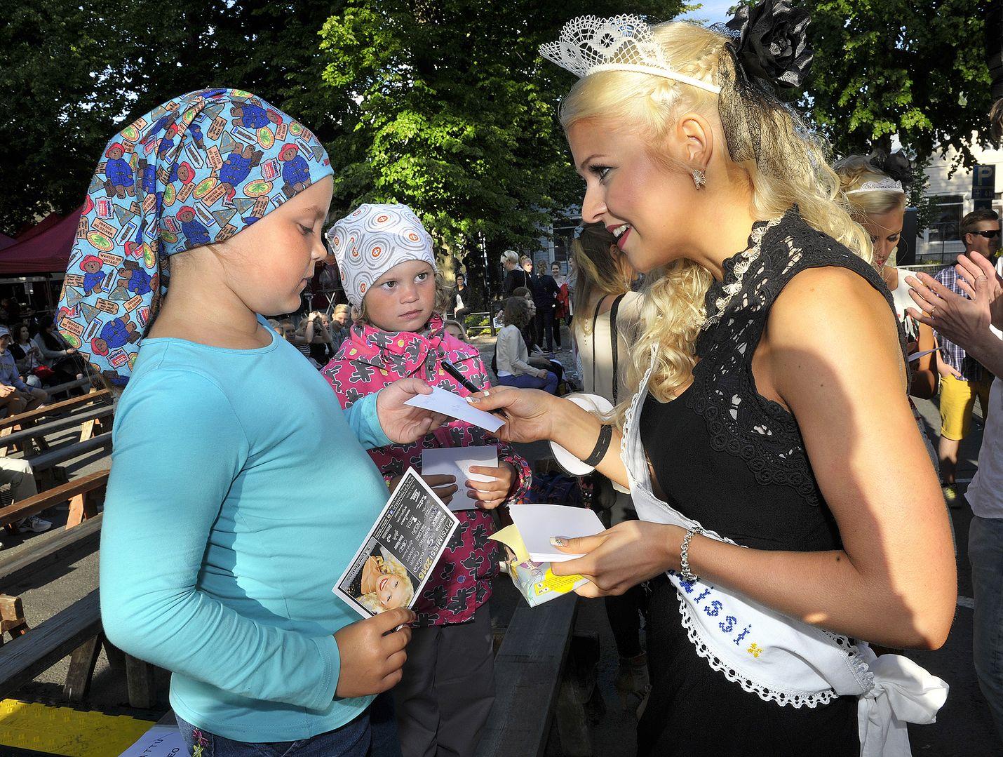 8-vuotias Jasmin Kestilä (edessä) oli aamusta asti halunnut katsomaan Pitsimissi-mittelöä. Myös tarkkaan missiä katsonut pikkusisko Julia sai Jenni Peräiseltä nimikirjoituksen.