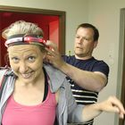 Teemu Knuutila asettaa päähäni pannan, joka tunnistaa pelaajaan kohdistuvat laukaukset. Kuva: Maija Männistö