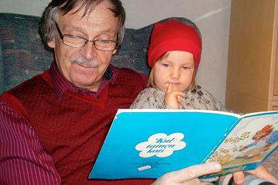 Pekka Pesonen lukee kirjaa lapsenlapsensa kanssa.