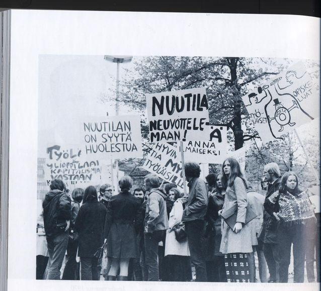 Anna Mauranen osallistui opiskeluaikoinaan aktiivisesti mielenilmauksiin. Kesäkuussa 1970 hän oli mukana mielenilmauksessa Helsingin rautatientorilla Nokian silloisen pääkonttorin Mikonlinnan edessä. Kylteissä esiintyvä Matti Nuutila oli Nokian kaapelitehtaan johtaja ja Nokian varatoimitusjohtaja. Menossa oli seitsemän viikkoa kestänyt Metallin lakko. Anna Mauranen on kuvassa ikkunaruutuhousuisen serkkunsa Marja Rostin takana. Kuva Martti Häikiön historiateoksesta Fuusio: Yhdistymisten kautta suomalaiseksi monialayritykseksi 1865–1982. Nokia Oyj:n historia 1, Edita 2001, s. 186.