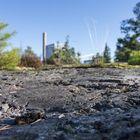 Raumalainen metsäteollisuus, kuten sellutehdas piippuineen, pilkottaa näköetäisyydellä Maanpään kallioilta pohjoiseen päin katsottuna. Kuva: Esa Urhonen