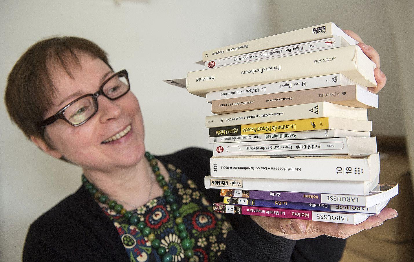 Osastonhoitaja Maisa Hyytinen esittelee ranskankielisten kirjojen pinoa. Nämäkin kirjat ovat tulleet Rauman kaupunginkirjastoon yksityisen henkilön lahjoituksena.