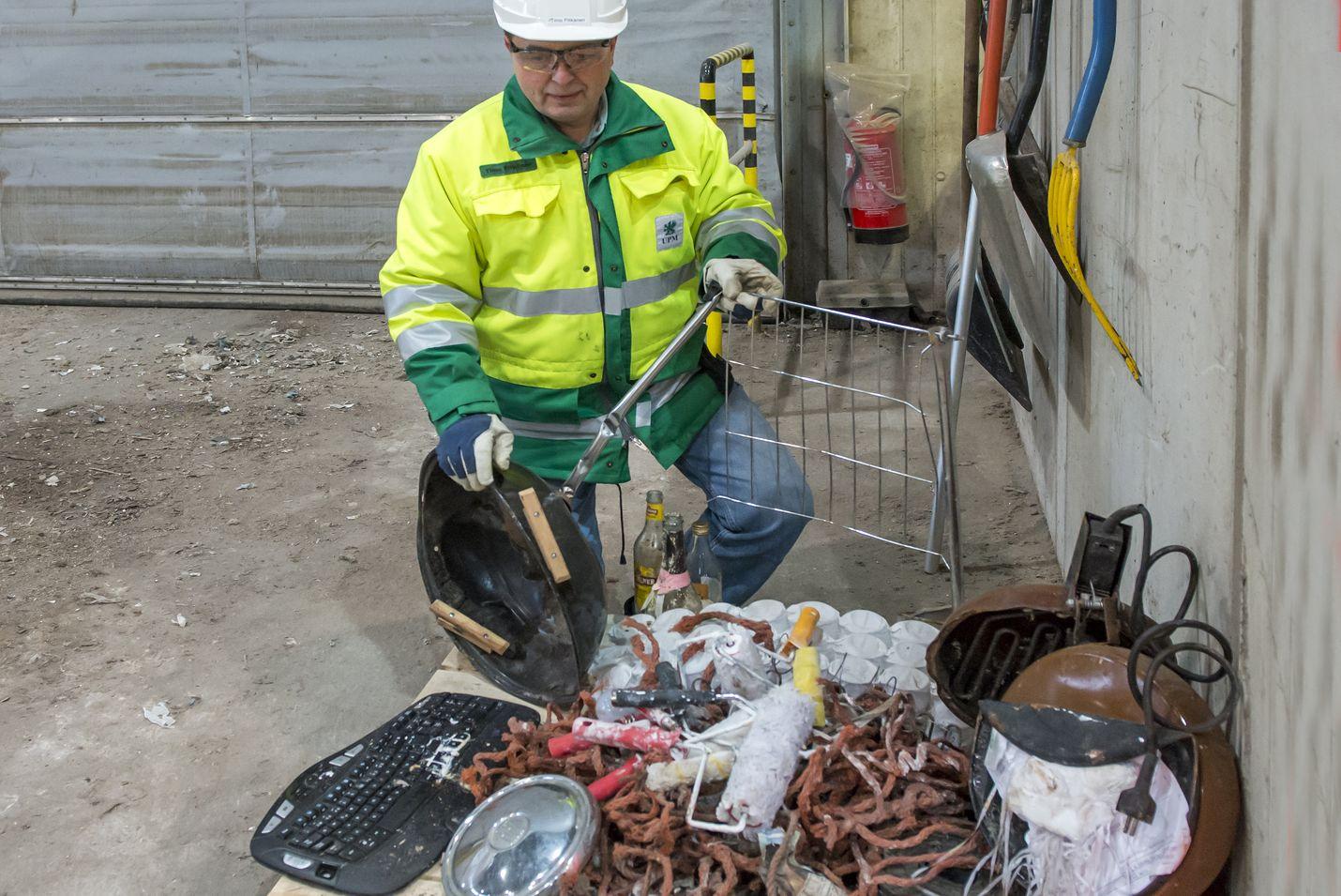 Rauman Biovoiman toimitusjohtaja Timo Pitkänen esitteli jätehallissa energiajätteen joukosta poimittuja tavaroita. Kasasta löytyi muun muassa pallogrilli ja tietokoneen näppäimistö.
