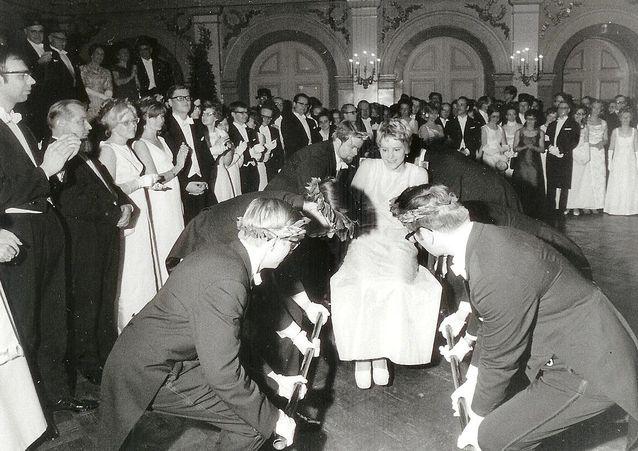 Seppeleensitojatar vuonna 1969. Vastaseppelöidyt maisterit kohottavat yleisen seppeleensitojattaren kantotuolissa.