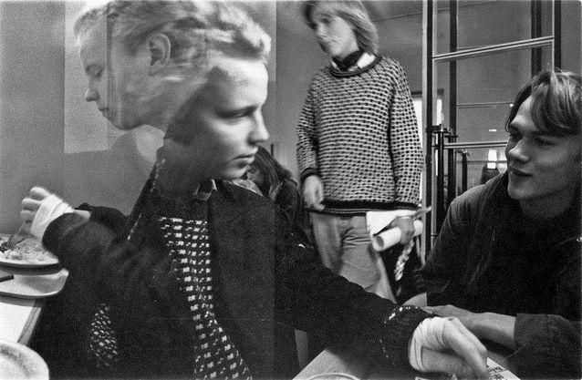 Nuorta humanismia Helsingin yliopiston päärakennuksen kahvilan tupakkahuoneessa 1979–1980 vaihteessa. Vasemmalla jo edesmennyt musiikkitieteen opiskelija Markku Honkanen, joka Taideteollisen korkeakoulun opintojen jälkeen ryhtyi dokumenttiohjaajaksi. Keskellä Kimmo Oksanen. Oikealla sellistiopiskelija Janne Varis. Kuvaajana toimi myöskin TaiKissa opiskellut Eero Könönen, joka sittemmin ryhtyi ohjaajaksi.
