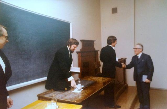 Akateemikko Oiva Ketonen onnittelee juuri väitellyttä Esa Saarista. Kuvassa keskellä on Ilkka Niiniluoto ja vasemmassa reunassa Jaakko Hintikka. Kuva on vuodelta 1977.