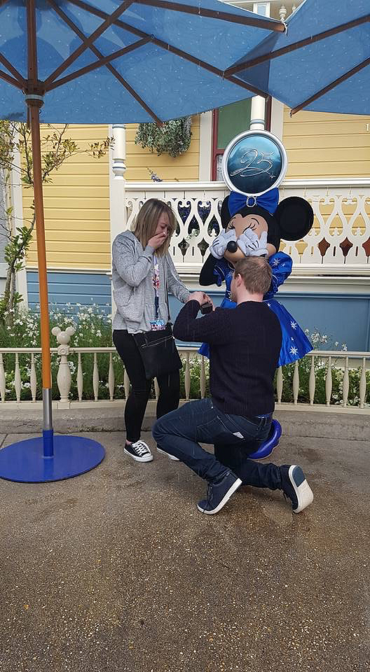 Lewis down on one knee proposing to Hannah in front of Minnie Mouse at Disney!