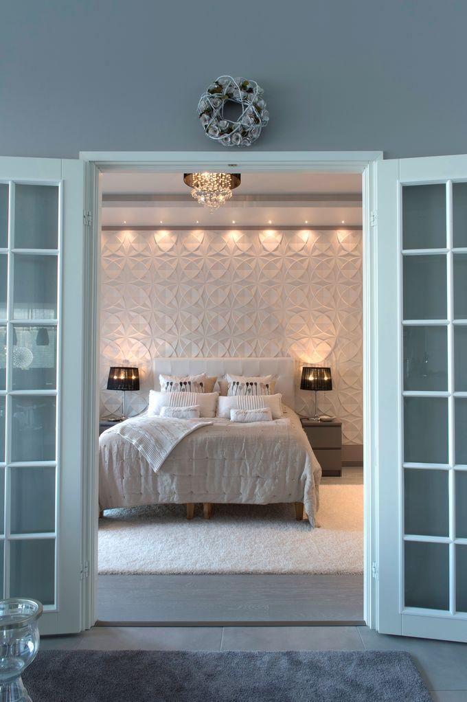 Makuuhuoneen kattoon on tehty reunoille alaslasku, josta tulee epäsuoraa valoa. Kolmiulotteista paneelia korostavat mini led-spotit. Tunnelmaa luovat koristeellinen kattovalaisin ja pöytävalaisimet. Design Heli Mäkiranta.