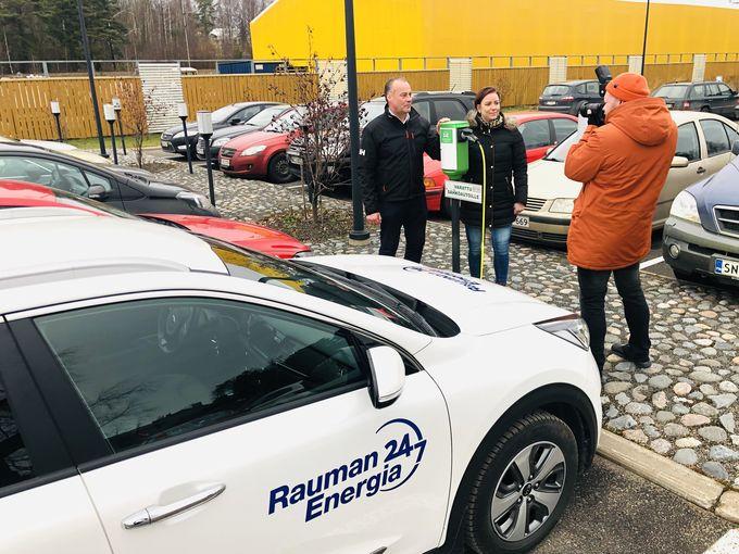 Juha Ahokas ja Susanna Tuominen kuvattavana Rauman Energian parkkipaikalla. Sähköautojen latausratkaisut taloyhtiöissä on nyt kuuma aihe.