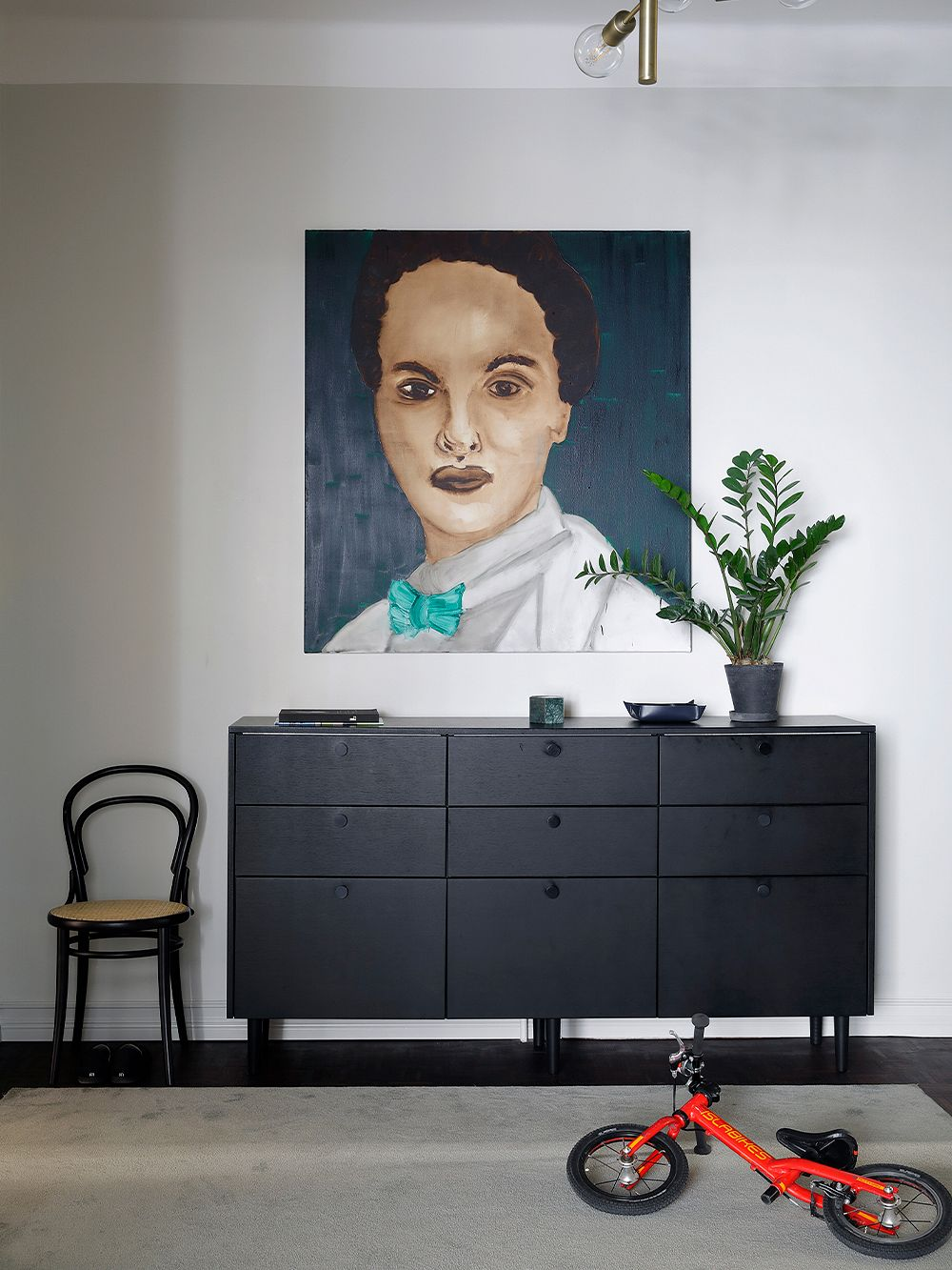 Black sideboard, red bicycle and a large portrait