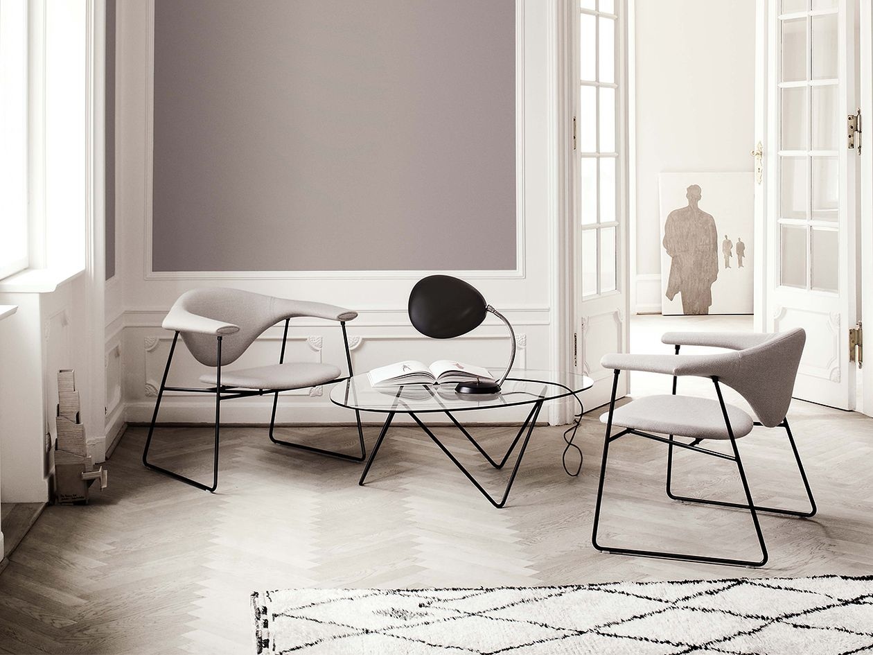 Gubi's Masculo-chairs, Pedrera coffee table and Cobra table lamp in a living room setting.