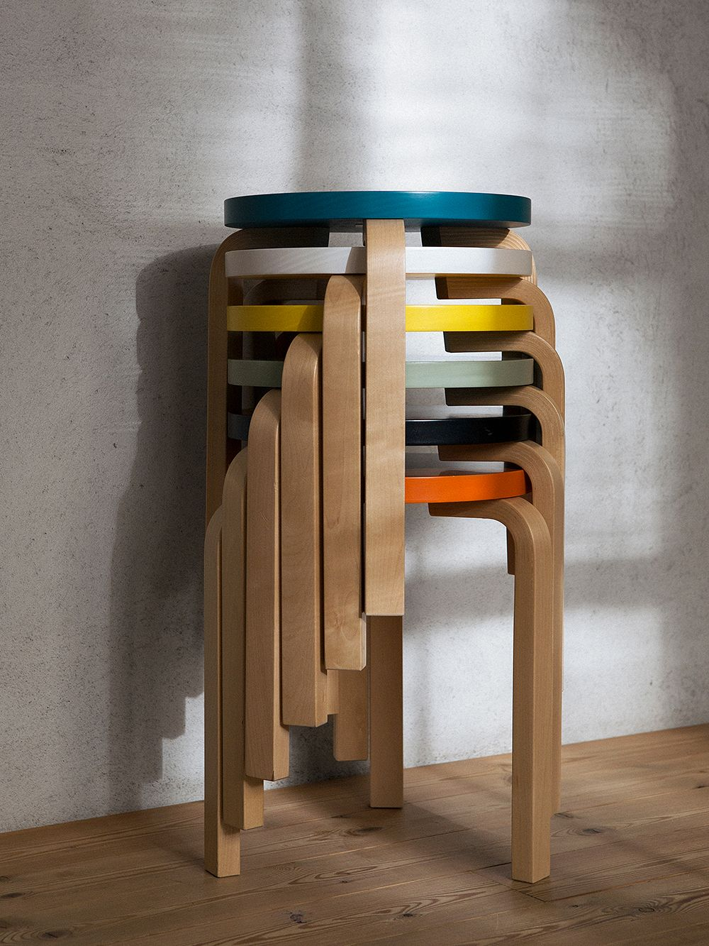 Artek's stool 60 stacked in a pile in different colors.