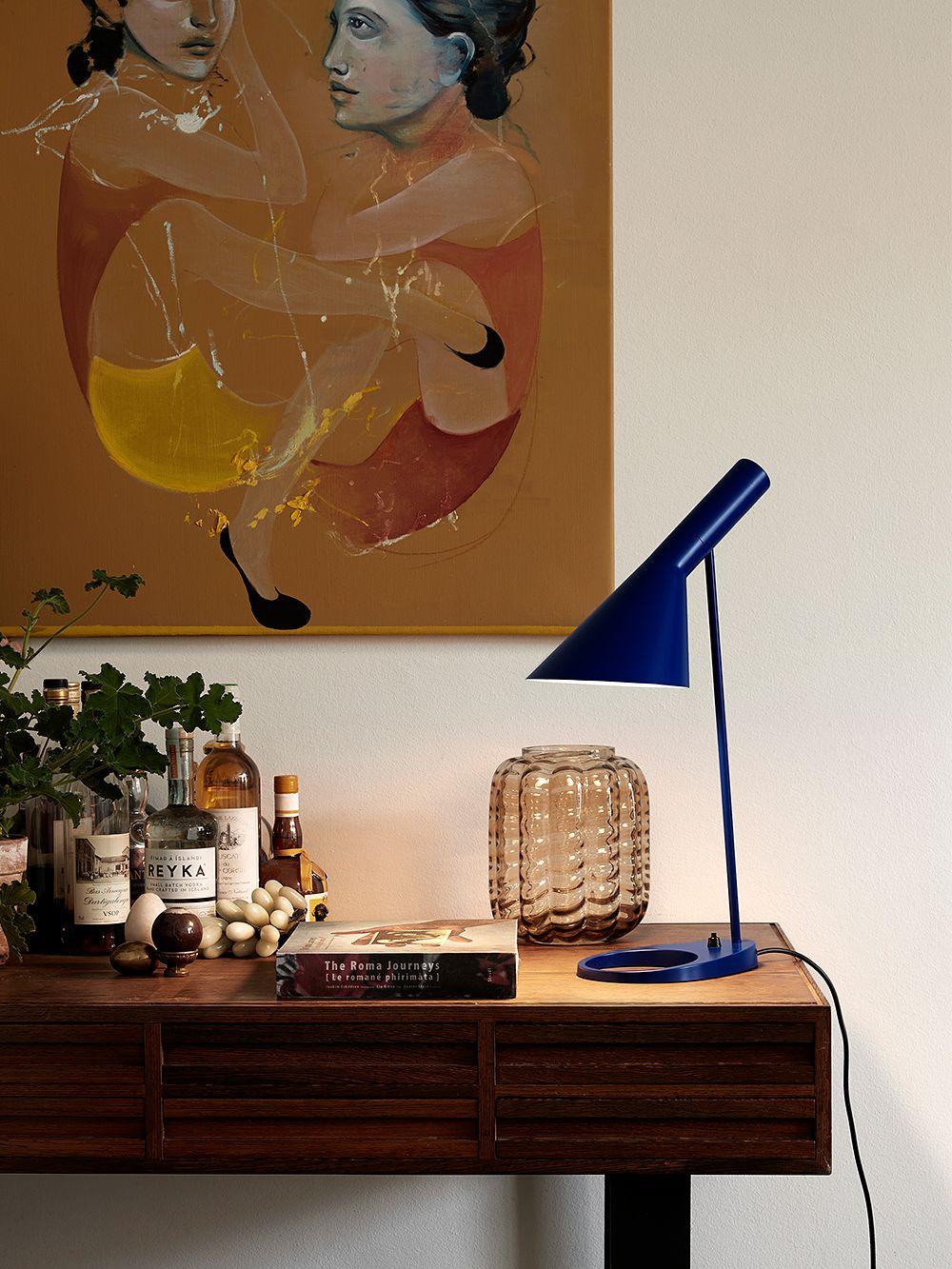 Louis Poulsen's AJ table lamp on a desk.