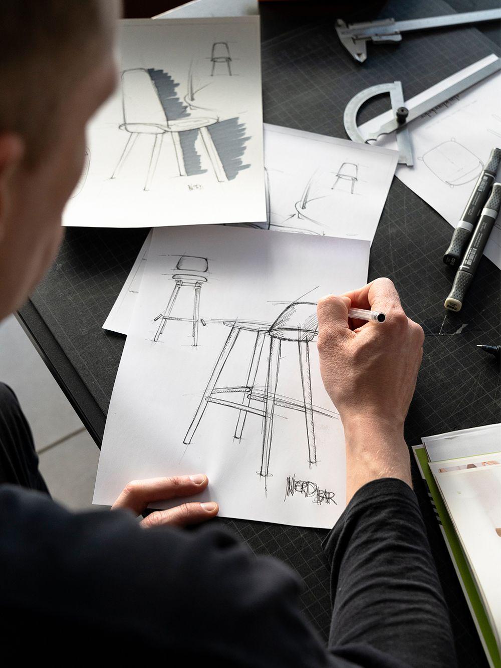 David Geckeler piirtopöytänsä ääressä hahmottelemassa luonnosta Nerd-baarituolista.