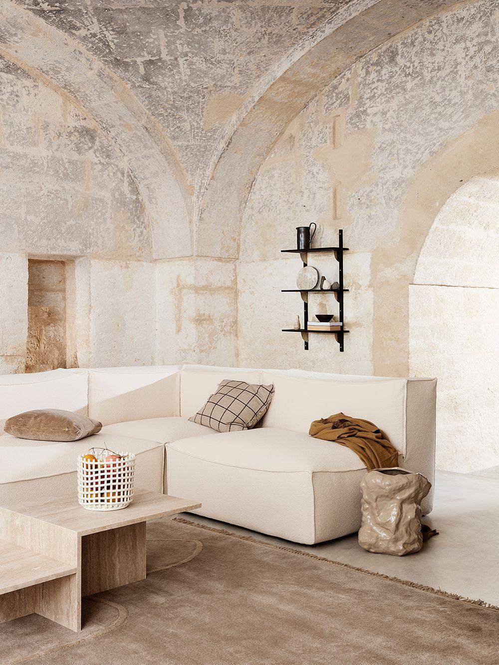Ferm Living's white Ceramic basket in a living room.
