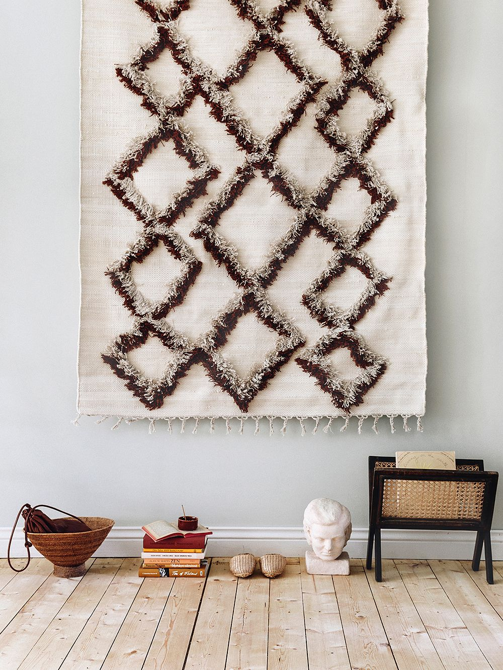 Finarte's Tie rug in brown, hung on the wall.
