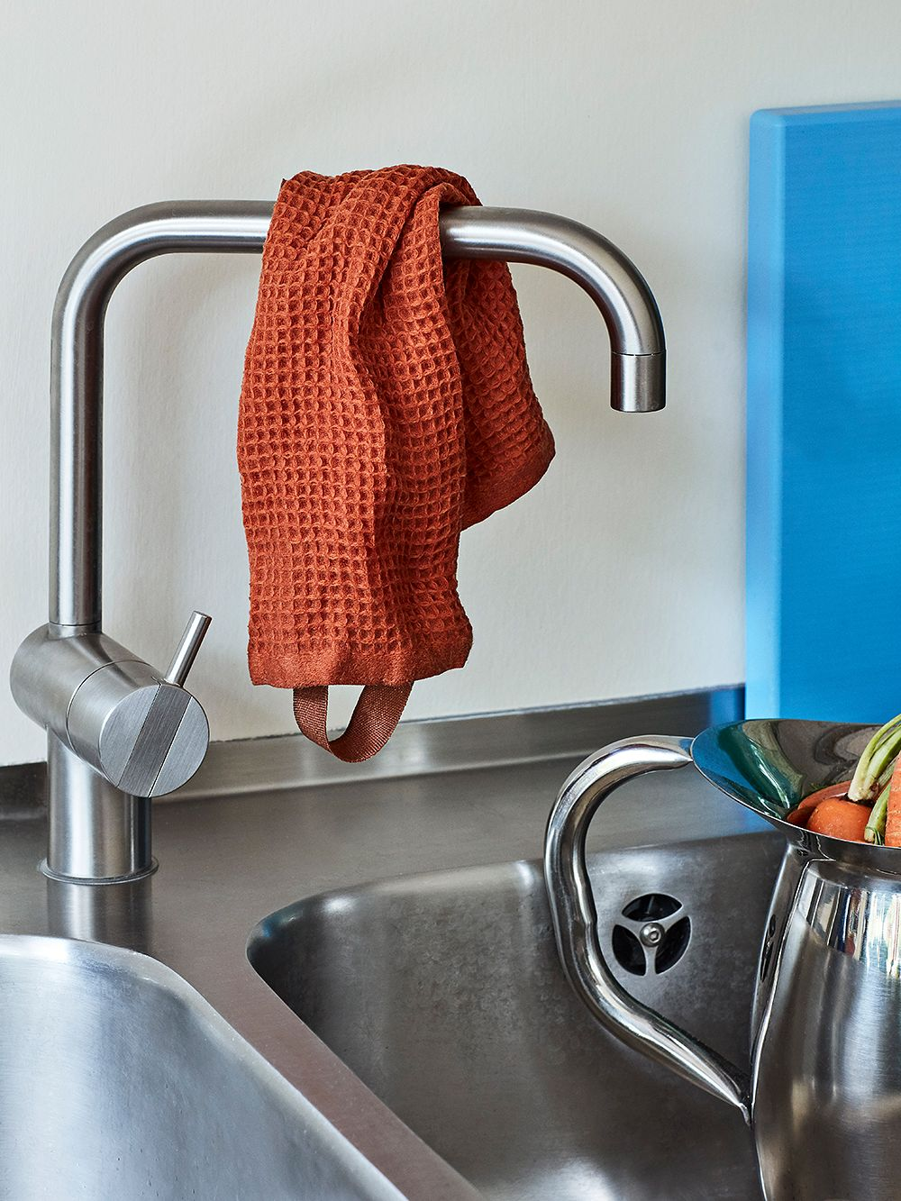 Hay's orange cotton dish cloth hanged over a faucet.