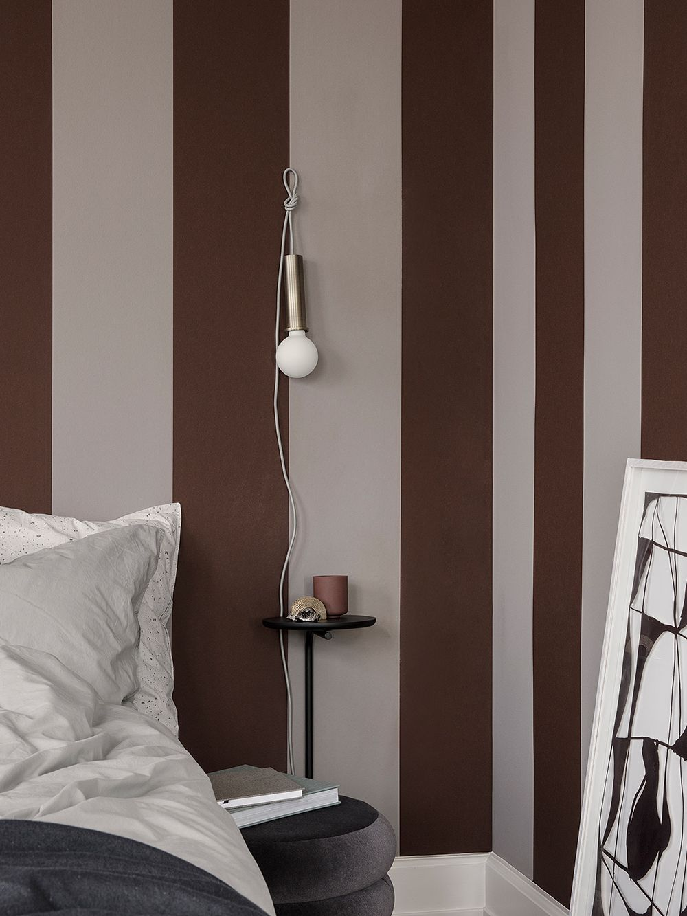 Ferm Living's Socket Pendant hung up on the wall in a bedroom.