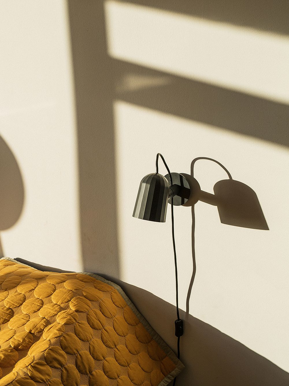 The Noc wall light by Hay in a dark grey color, attached to a bedroom wall.